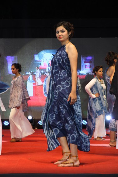 Stitched circles float across the front of Dr. Reena Bhatia's garment in deep shades of indigo blue.